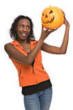 Young woman with jack-o-lantern. Happy young African-American woman holding jack-o-lantern royalty free stock photo