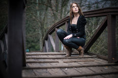 Young woman in jacket crouch at bridge Stock Photo