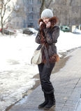 The young woman in a jacket with a fur collar on the street in the winter. Stock Photo