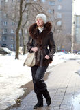 The young woman in a jacket with a fur collar in the winter in a sunny day Stock Photography