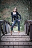 Young woman in jacket standing at the bridge. Young woman standing at the bridge Royalty Free Stock Photo