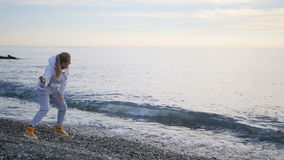 Young woman in jacket throwing pebbles into ocean, foamy waves splashing ashore stock video footage