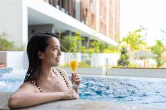 Young Woman in jacuzzi pool and enjoy drink Stock Image