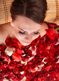 Young woman in jacuzzi with rose petal. Royalty Free Stock Image
