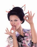 Young woman in Japanese kimono with chopsticks and sushi roll. Royalty Free Stock Photos