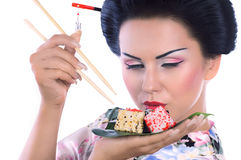 Young woman in Japanese kimono with chopsticks and sushi roll. Royalty Free Stock Photo