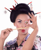 Young woman in Japanese kimono with chopsticks and sushi roll. Stock Photography