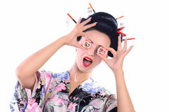 Young woman in Japanese kimono with chopsticks and sushi roll. Stock Photo