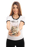 Young woman with a jar filled with money Stock Image