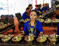 Young woman in Javanese clothing playing gamelan . A young woman in Javanese clothing playing gamelan accompanied by his peers in the team seen in the Royalty Free Stock Photos
