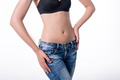 Young woman in jeans with beautiful flat belly. Young woman in jeans with beautiful flat belly Stock Photo