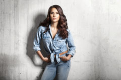 Young woman in jeans and a denim shirt. Beautiful brunette cutly hair young woman in jeans and a denim shirt on gray cement background Stock Image