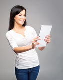 Young woman in jeans holding a tablet Stock Photos