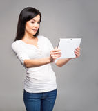 Young woman in jeans holding a tablet Royalty Free Stock Photography