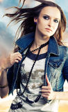 Young woman in jeans jacket. Girl with flying hair  holding beads in jeans jacket on the abstract background Royalty Free Stock Photos