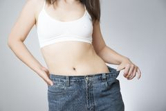 Young woman in jeans of large size, concept of weight loss Stock Photos