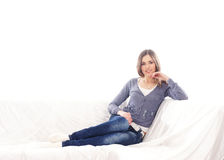 A young woman in jeans laying on a white sofa Stock Photos
