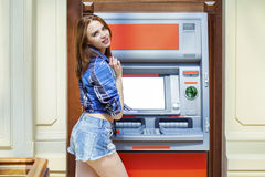 Young woman in jeans short using an automated teller machine Royalty Free Stock Photo