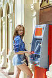 Young woman in jeans short using an automated teller machine Royalty Free Stock Image