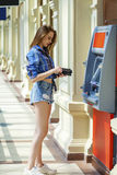 Young woman in jeans short using an automated teller machine. Brunette young lady using an automated teller machine . Woman withdrawing money or checking account Royalty Free Stock Photos