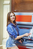 Young woman in jeans short using an automated teller machine Royalty Free Stock Photography