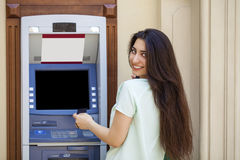 Young woman in jeans short using an automated teller machine Stock Images