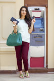 Young woman in jeans short using an automated teller machine Stock Photography