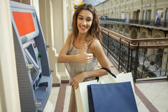 Young woman in jeans short using an automated teller machine Royalty Free Stock Images
