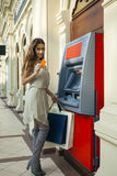 Young woman in jeans short using an automated teller machine Stock Photo