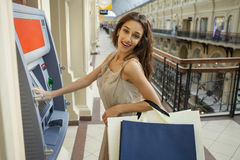 Young woman in jeans short using an automated teller machine Stock Image
