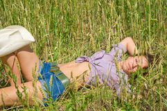 The young woman in jeans shorts lies in the field. Stock Photo