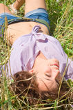 The young woman in jeans shorts lies in the field. Stock Image
