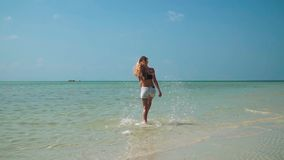 Young woman in jeans shorts walking at shallow tropical sea. Young Woman Walkng at Shallow Tropical Sea shot with a Sony a6300 fps29,97 FHD stock footage