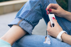Young woman in jeans sitting on the bench and connect the headph. A young woman in jeans sitting on the bench and connect the headphones to her music player Stock Photography