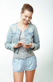 Young Woman in Jeans with Smartphone Royalty Free Stock Images