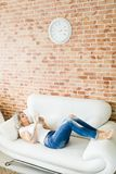 Young woman in jeans using smart phone comfortably lying on white sofa. Brick wall in background stock photos