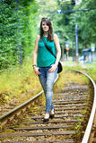 Young woman in jeans walking along a railroad Stock Photos