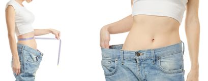 Young woman in jeans weight loss weight loss with a centimeter set. On a white background isolation Stock Image