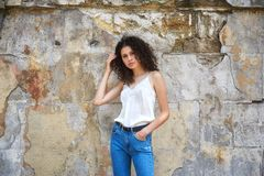 Young beautiful woman in jeans and white blouse on old city street royalty free stock photo