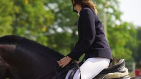 A young woman jockey on the horse performs at equestrian competitions.
