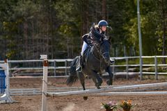 A young woman jockey on a horse performs a jump across the barrier. Competitions in equestrian sport. Close-up royalty free stock photography