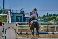 A young woman jockey on a horse performs a jump across the barrier. Competitions in equestrian sport. Close-up stock images