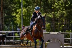 A young woman jockey on a horse performs a jump across the barrier. Competitions in equestrian sport. Close-up royalty free stock photos