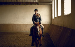 Young woman jockey sitting on brown horse at indoor arena Stock Photography