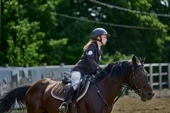 Young woman jockey in white black dress and black boots, takes part in equestrian competitions. Sunny summer day. Close-up royalty free stock photo