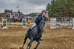 Young woman jockey in white black dress and black boots  takes part in equestrian competitions.  stock photo