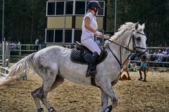 Young woman jockey in white dress and black boots  takes part in equestrian competitions. Close-up royalty free stock image