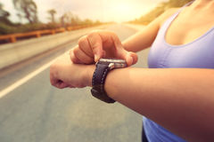 Young woman jogger ready to run set and looking at sports smart watch Stock Image