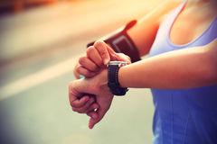Young woman jogger ready to run set and looking at sports smart watch. Checking performance or heart rate pulse trace. Sport and fitness outdoors in city Stock Photography