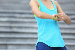 Young woman jogger ready to run set and looking at sports smart watch Royalty Free Stock Photos